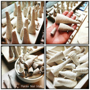 Ceramic clay rolled out into cones, holes added, set up to dry, then bisque fire.