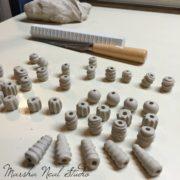 Texturing ceramic clay to make beads.